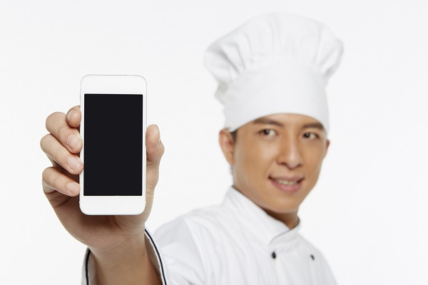 Chef holding up a mobile phone