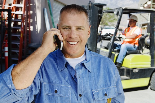 Man talking on mobile phone with another steering forklift truck on background