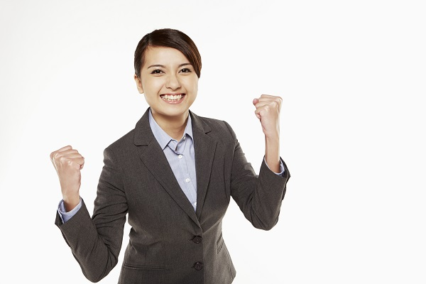Businesswoman cheering with fists in the air