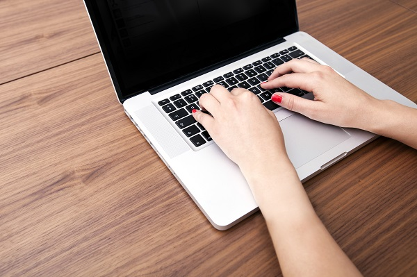 Close-up of businesswoman's hands using laptop at table